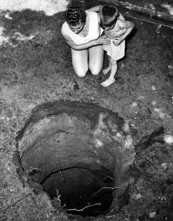 George Brich Mrs. Robert McConnell and son Robert Jr. peer into strange 14 foot cave-in in backyard of their home centre de la terre.jpg