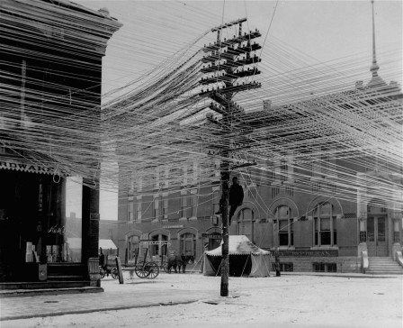 Telephone_lines_at_an_intersection_in_Pratt_Kansas_USA_1911_le_reseau_telephonique_toile_web.jpg