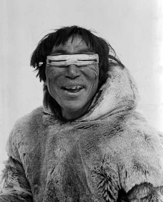 Smiling Inuit man wearing bone snow goggles lunettes froid hiver ski.jpg