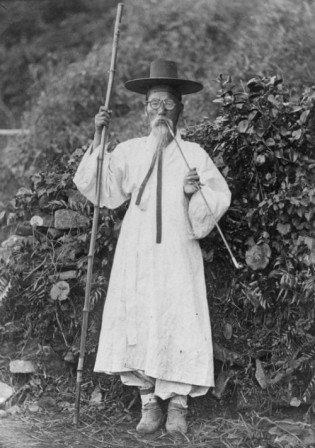 A Korean man in traditional robe and boots (hanbok), wearing a horse hair and bamboo hat (gat), holding a staff and smoking a pipe. 1885.jpg, sept. 2019